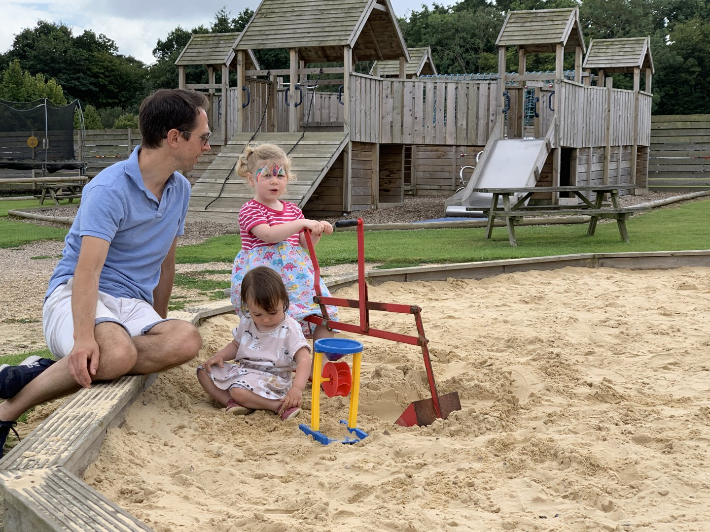 M and B play in the sandpit as Matthew sits on the side, chatting to them.