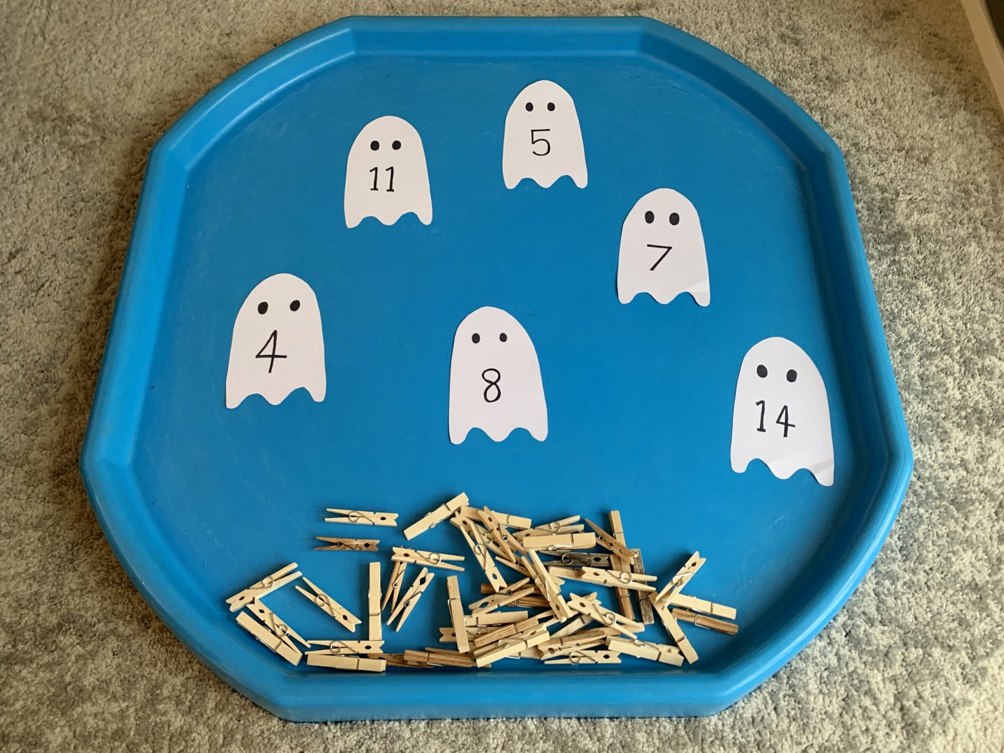 Six number ghosts sit in a blue tuff spot, with a pile of pegs underneath them.