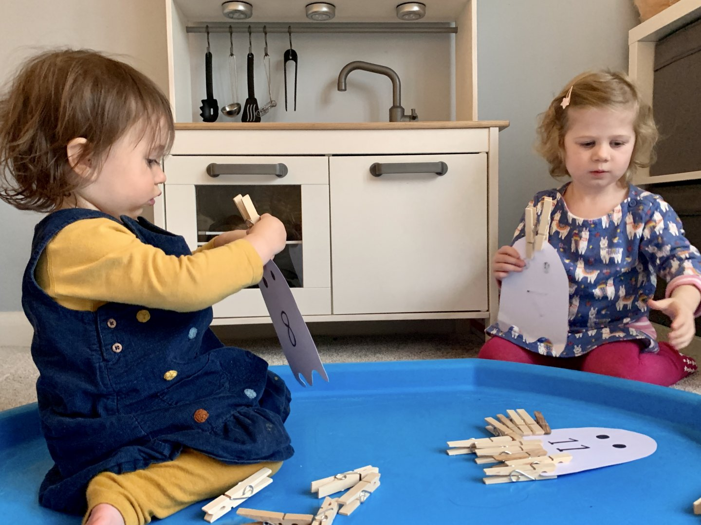 B sits in the centre of the tuff spot, trying to clip a peg onto a ghost. M sits to the right hand side of the tuff spot, holding her cardboard peg ghost in one hand, while reaching for a peg with the other hand.