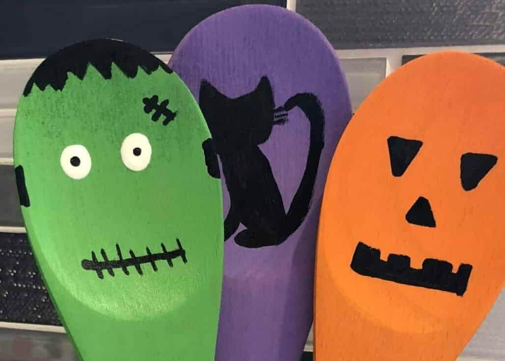 Three wooden halloween spoons decorated as a monster, a cat and a pumpkin.