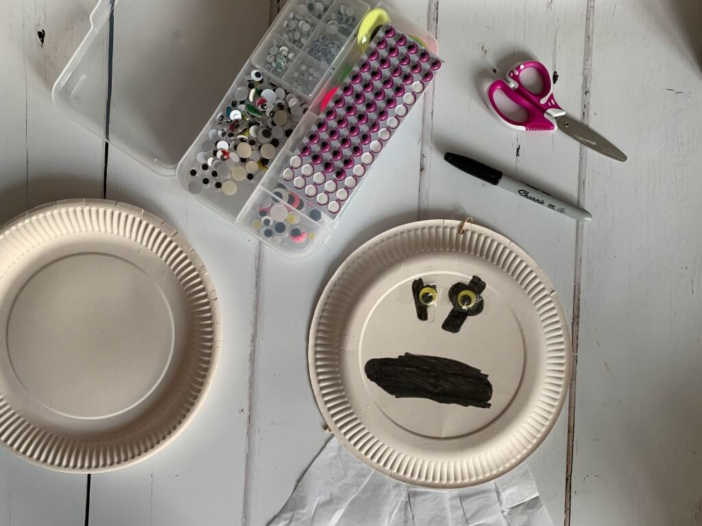 A paper plate ghost with googly eyes and tissue paper body surrounded by craft equipment.