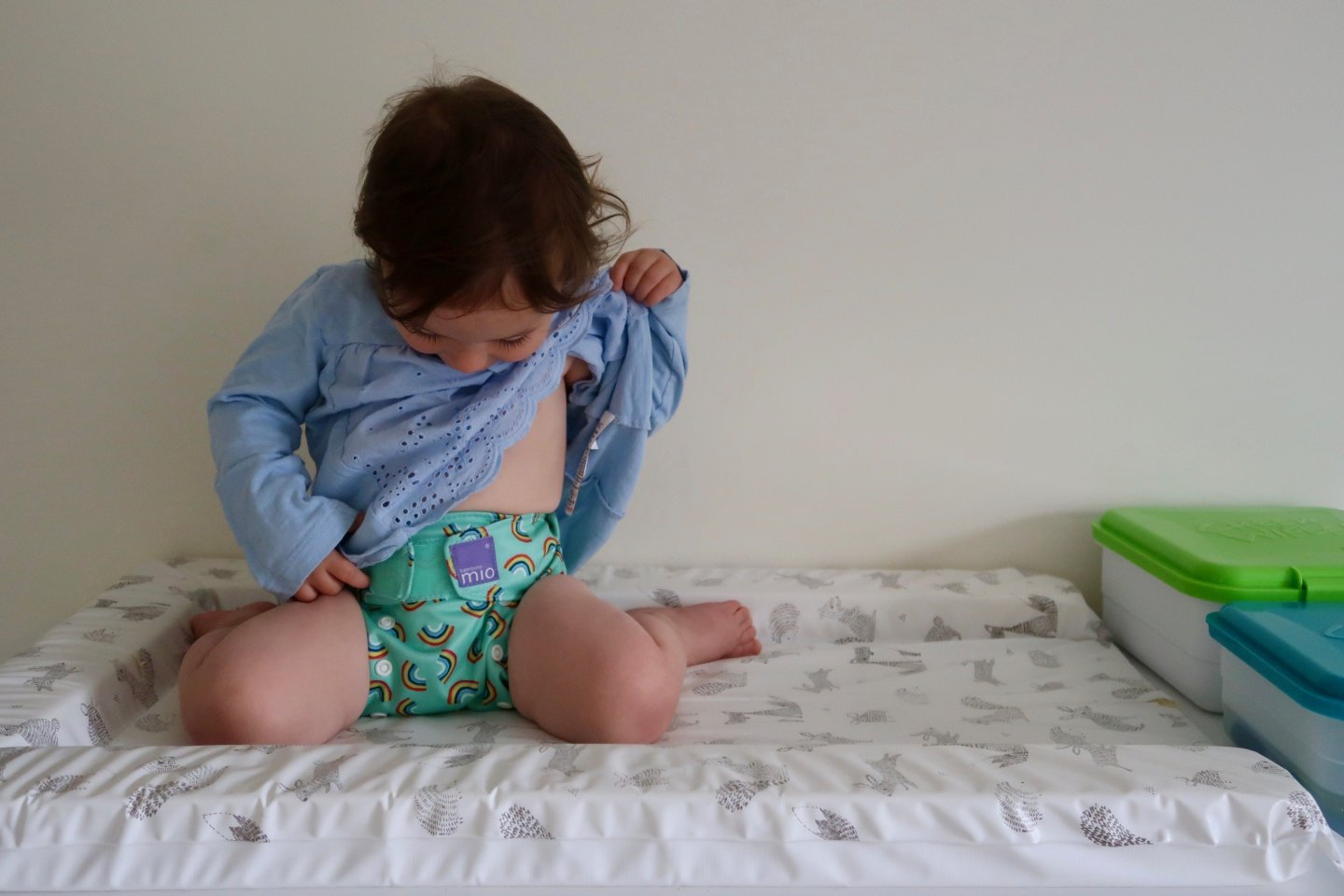 B sits on top of the changing mat, lifting up her top to look at her colourful reusable nappy. The Cheeky wipes boxes are on the changing table, next to her.