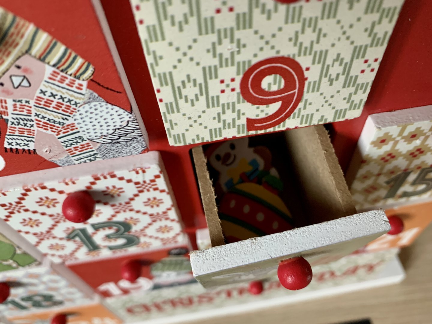 A drawer of the advent house is open to reveal two Christmas stickers inside.