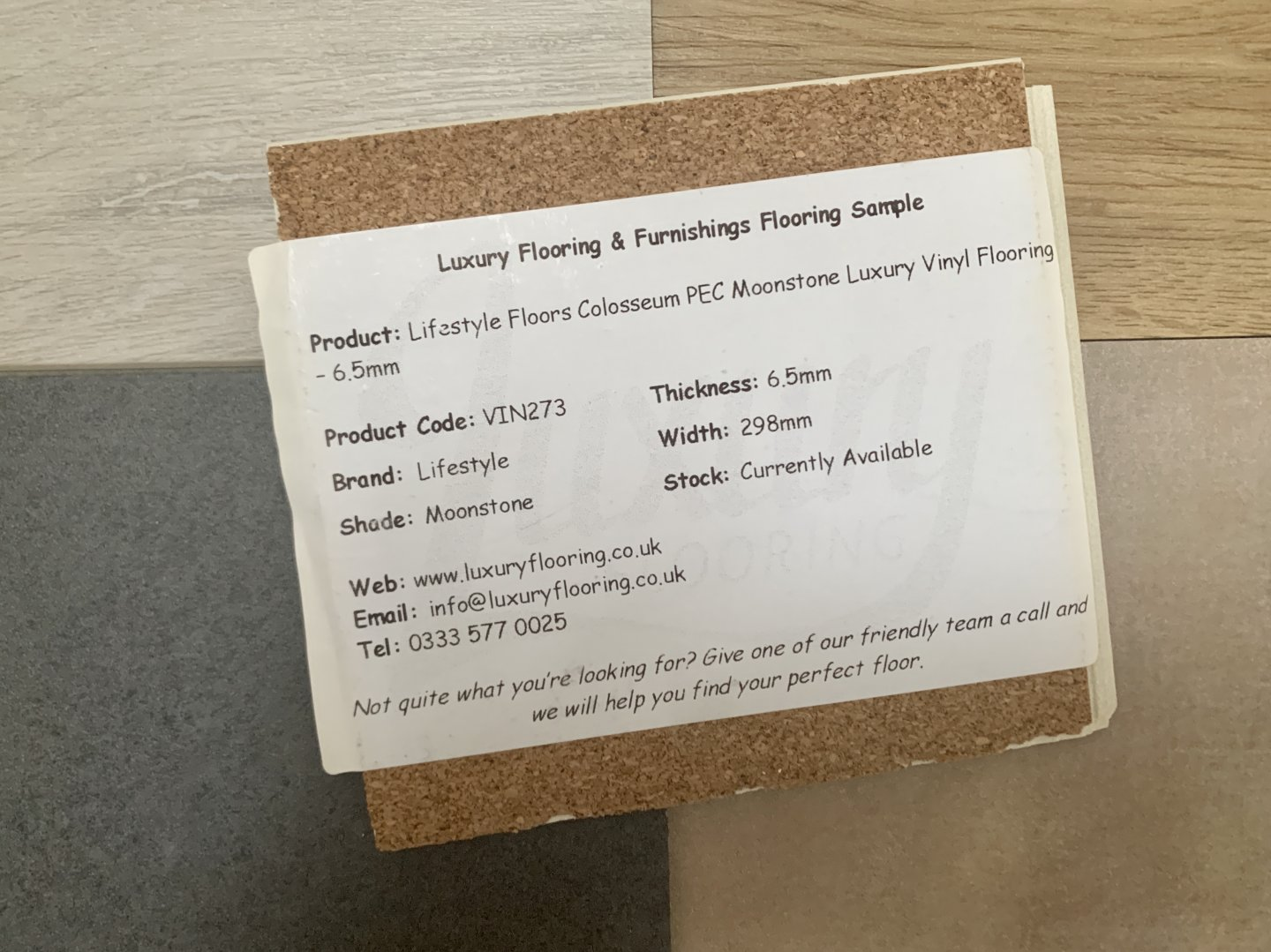 An image showing the information sticker on the back of a sample of LVT from Luxury Flooring. Includes order details, thickness, width, shade and brand information.